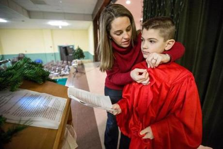Gretchen Reynard helps son Jack, 8, put on his robe before the Nativity play at St. Mary's Parish in East Walpole.